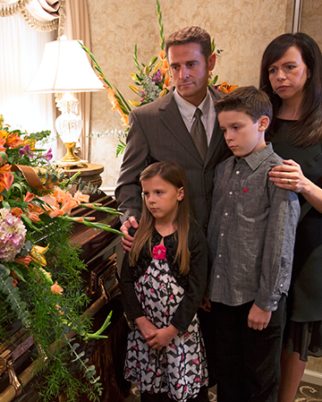 Family surrounding a casket with a floral spread